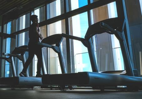 fitness center with man running on treadmill
