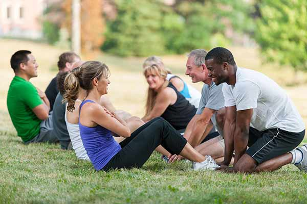 group of gym members working out in a park