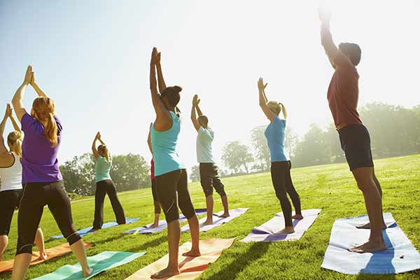 group yoga class outdoors in a park