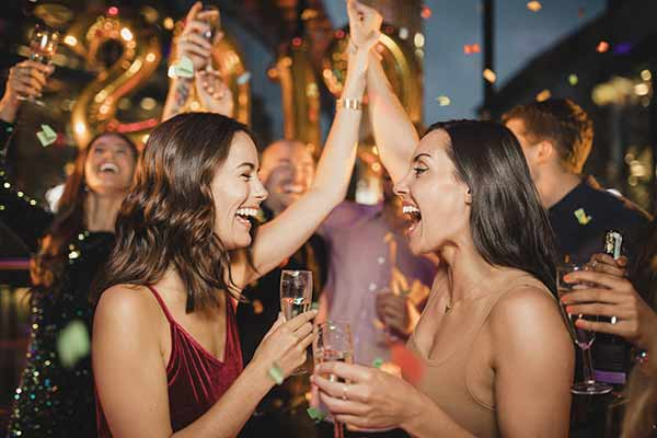 2 women high five each other as new year turns