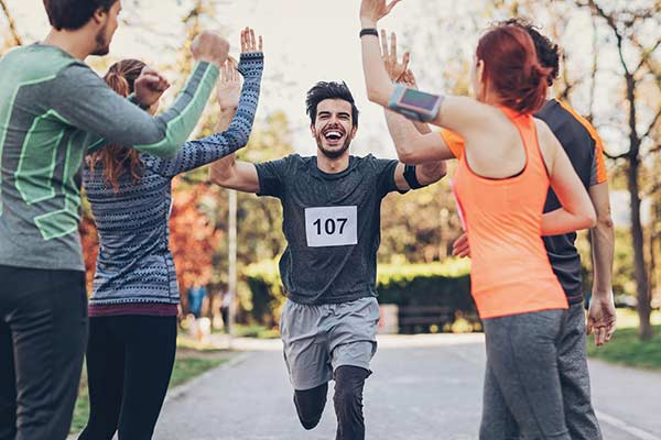 man getting high fived as he finishes a 5k