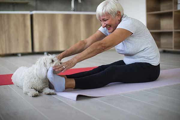senior woman doing stretch with her dog