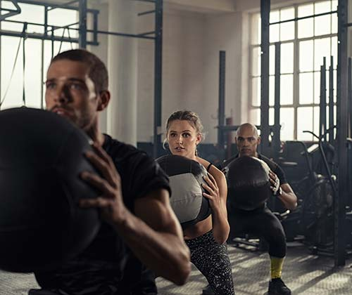 3 people in a small gym working with a medicine ball