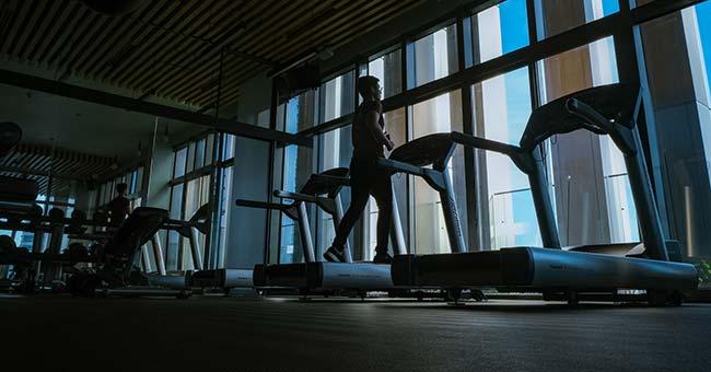 man running on treadmill in empty gym